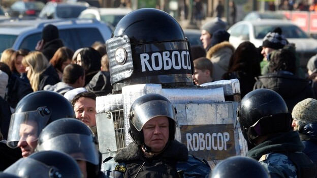 A protester wearing a costume bearing the words Robocop walks among Russian riot police officers after a rally in Moscow on Saturday. (AP)