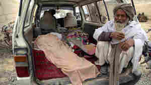 An elderly Afghan man sits next to the covered body of a person who was allegedly killed by a U.S. service member in Panjwai, Kandahar province south of Kabul, Afghanistan, on Sunday, March 11, 2012.