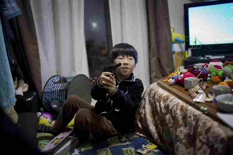 Mitsuhiro Abe, 7, who lives in temporary housing with his grandmother and parents, plays with a toy gun in the family's living room.