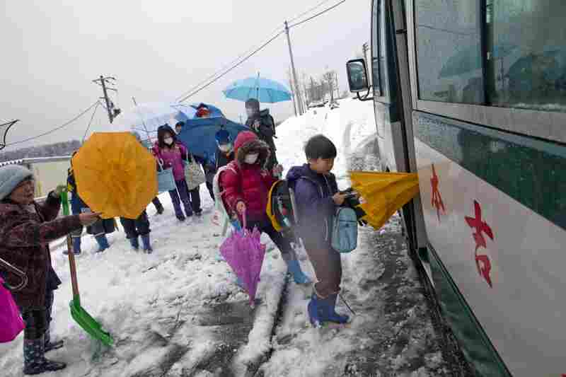 Children who are still displaced catch the bus to school.