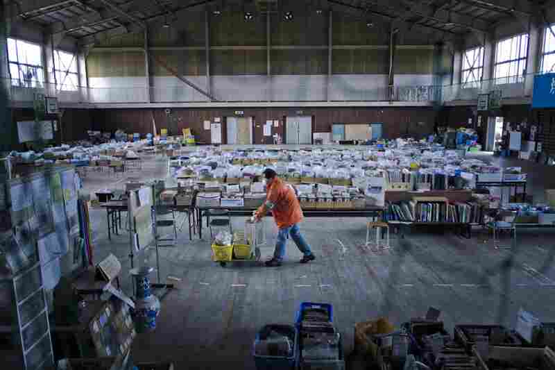 A volunteer wheels unclaimed articles inside the gym. Volunteers help clean, catalog and store the found items.