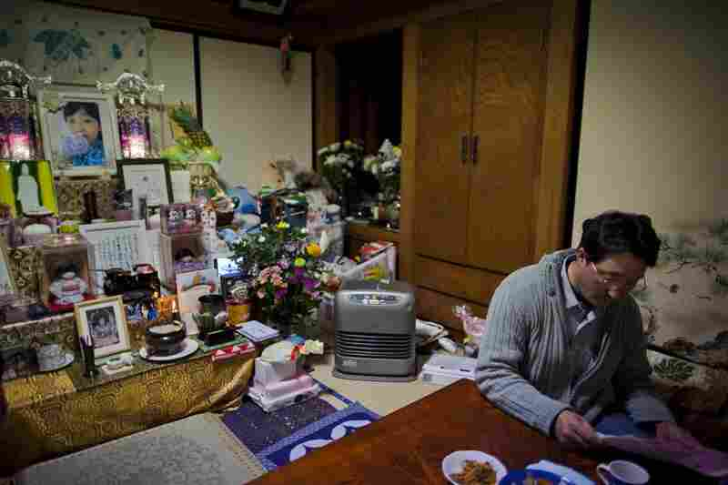 Takahiro Shito, 47, sits at home next to a Buddhist altar dedicated to his daugher, 11-year-old Chisato, who was killed during last year's tsunami at Okawa Elementary School in Ishinomaki.