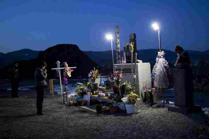 A woman prays at a shrine commemorating the victims of the Okawa tragedy.