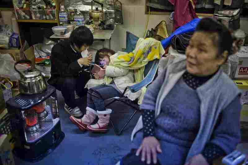Kikuko Abe, 65, looks on as her grandchildren, Iroha Kodama, 8, and Naiki Kodama, 15, play hand-held video games in a temporary community center.