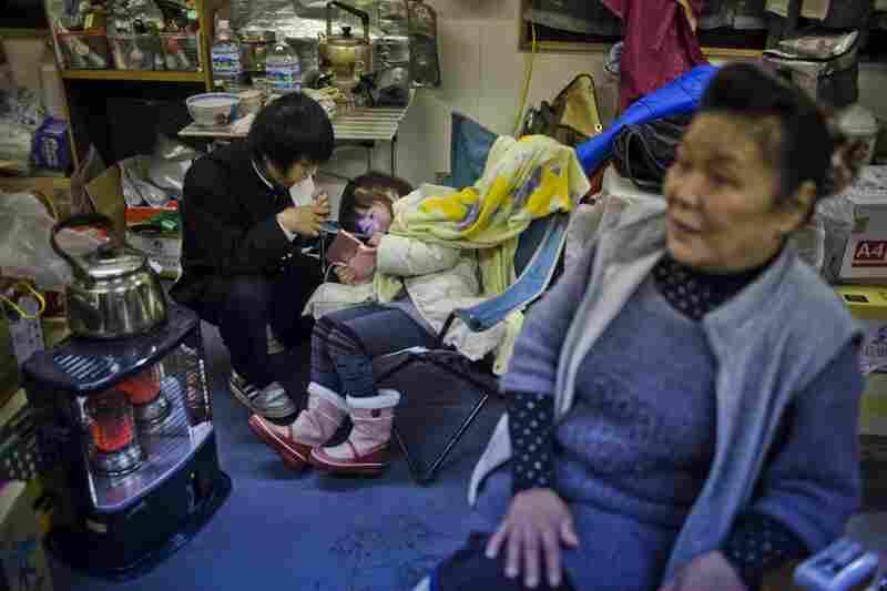 Kikuko Abe, 65, looks on as her grandchildren, Iroha Kodama, 8, and Naiki Kodama, 15, play hand-held video games in a temporary community center.