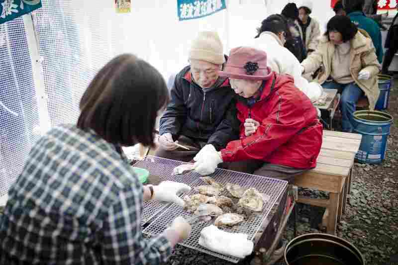 Shiro Uwano, 82, and Reiko Uwano, 76, eat charcoal grilled oysters at Ishinomaki's only functioning restaurant. On this day, the wait for a seat was more than hour.