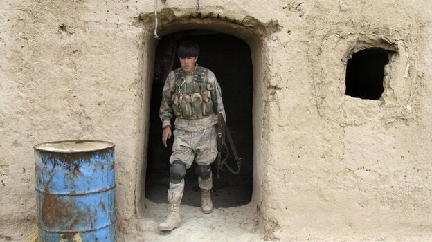 The deaths of Afghan civilians, who were allegedly shot by an American soldier, could make the U.S. mission even harder. Here, an Afghan soldier leaves a home where civilians were killed Sunday in the southern province of Kandahar.