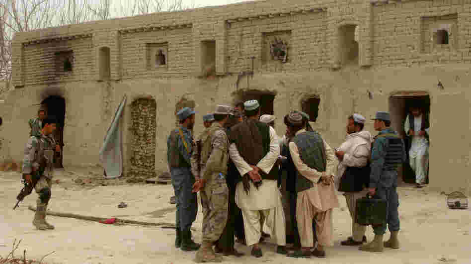 Afghan civilians and soldiers gather outside a home where Afghans were shot dead on Sunday, allegedly by a U.S. serviceman, in the Panjwayi district in southern Afghanistan.