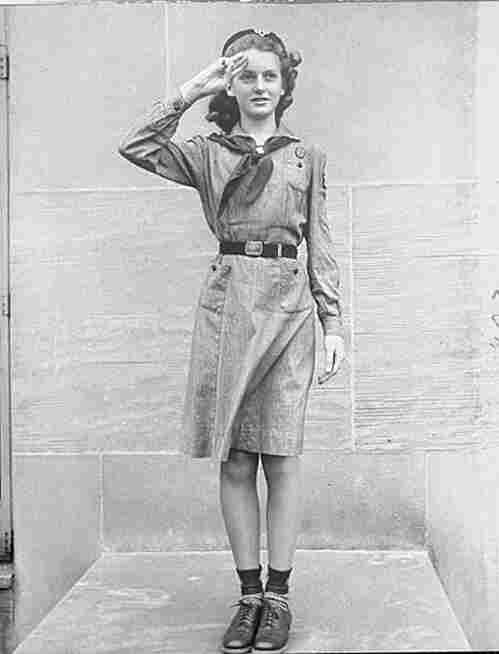 A Girl Scout salutes the flag with three fingers, New York, January 1940