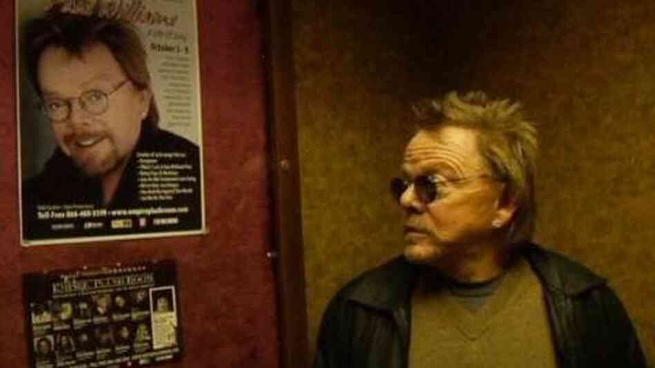 Paul Williams stares at a poster advertising an upcoming performance in the documentary Paul Williams Still Alive.