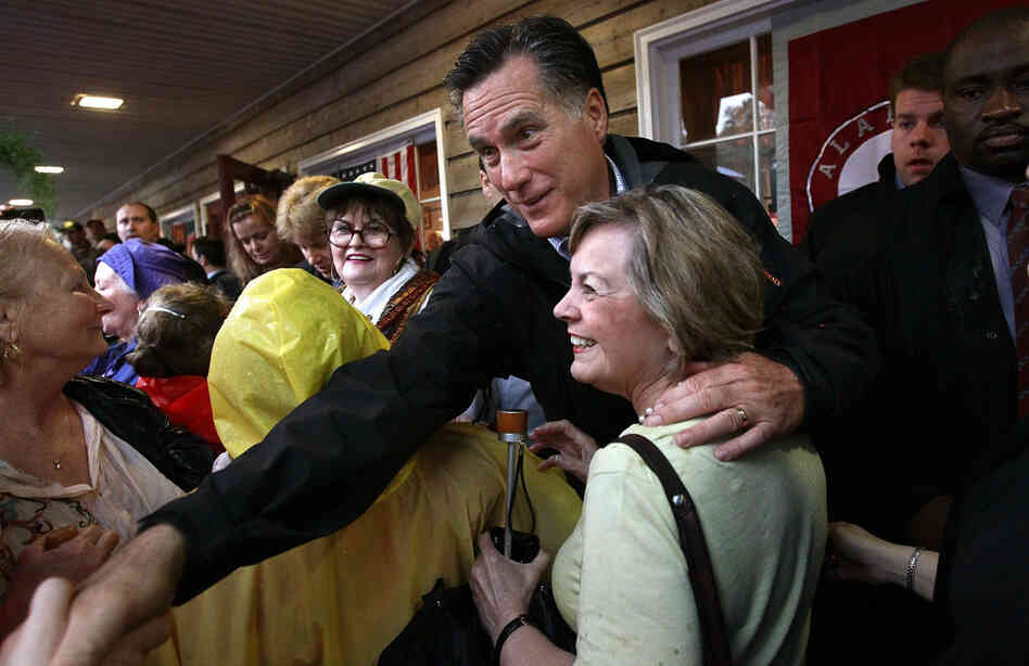 Republican presidential candidate Mitt Romney greets supporters at the Whistle Stop cafe in Mobile, Ala., on Monday, his birthday.