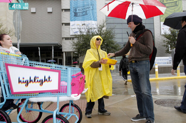 """Jessica Weaver, center, hands out trinkets advertising the new mobile app """"Highlight"""" to passers-by outside the SXSW Interactive Festival and Conference in Austin, Texas on Saturday."""