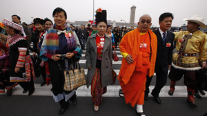 Delegates wear the traditional garb of their ethnic minority — the Burberry bag at left (estimated cost: $800) notwithstanding — in Beijing on March 3.