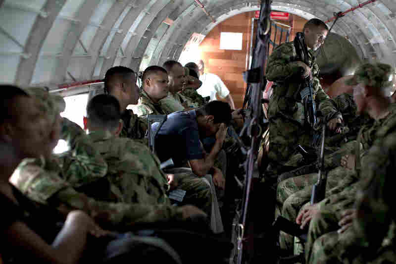 Colombian infantry troops and civilian passengers rest during a flight.