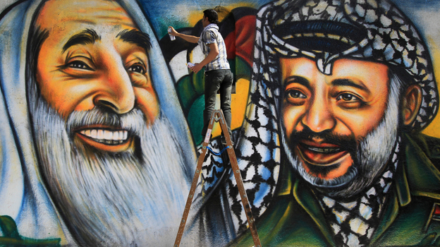 Palestinian artist Mohammed al-Dairi paints a mural of late Palestinian leader Yasser Arafat (right) and late Hamas leader Sheikh Ahmed Yassin (left), in Gaza City. Hamas leaders are divided on what direction to take the Islamist movement, with some calling for reconciliation with Arafat's Fatah movement. (AFP/Getty Images)