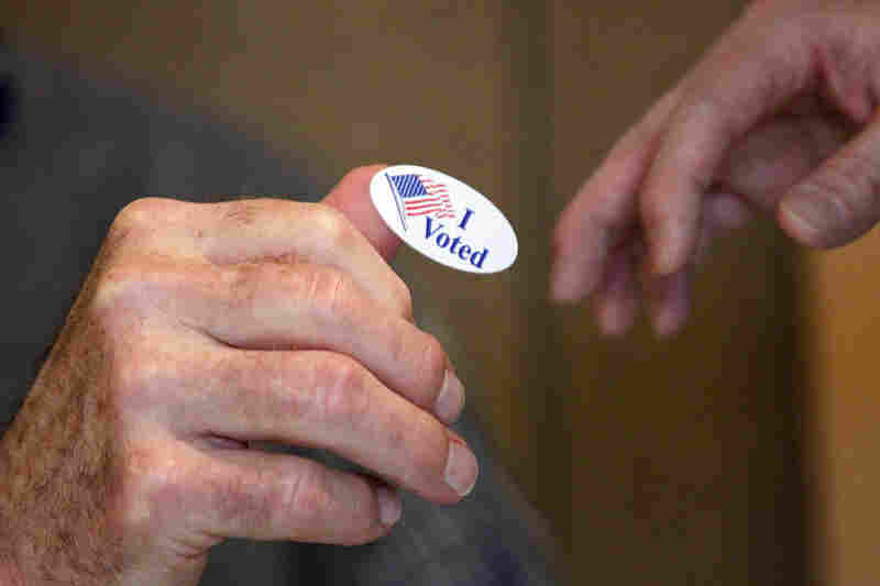 "Madison United Methodist Church precinct worker Bob Shirley hands a ""I Voted"" sticker to a voter in"