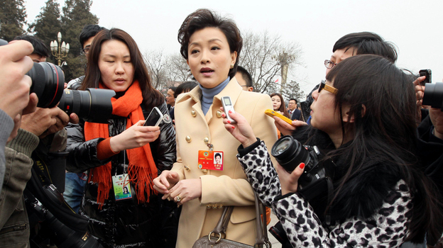 """Yang Lan, TV host and delegate to the Chinese People's Political Consultative Conference, carries a Marc Jacobs handbag outside the Great Hall of the People in Beijing on March 3. Nicknamed """"the Oprah Winfrey of China,"""" Yang has also been seen wearing a Giorgio Armani jacket during the legislative session.  (AP)"""