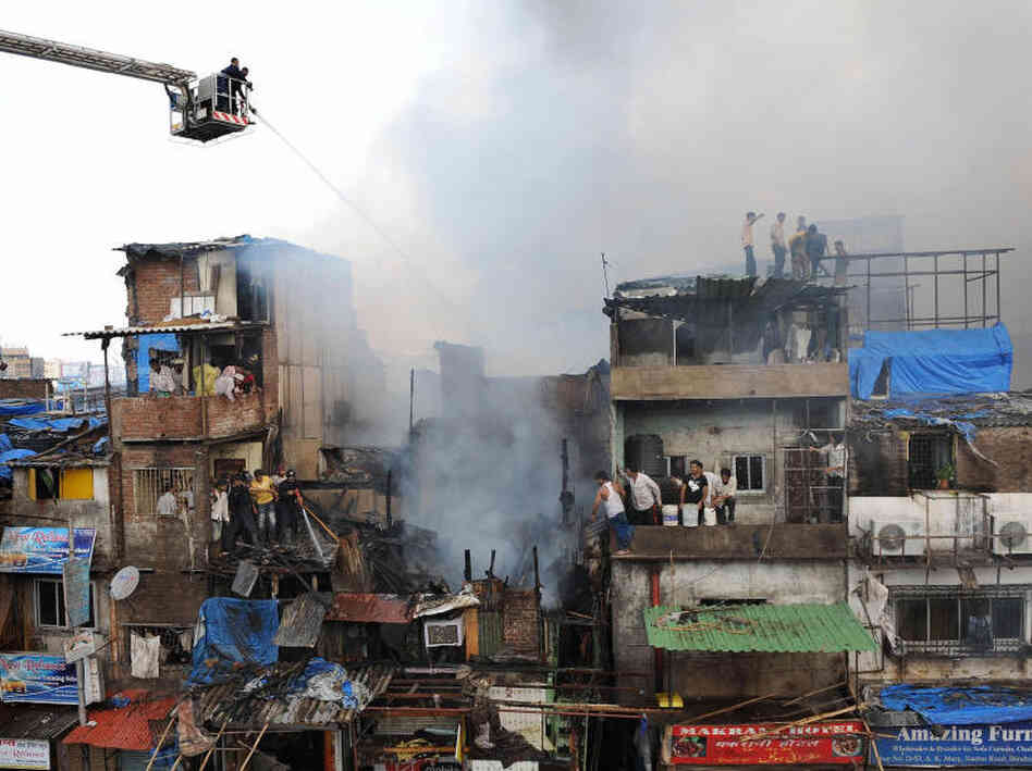 Indian fire brigade officials use water jets to control a fire in the Garibnagar slums.