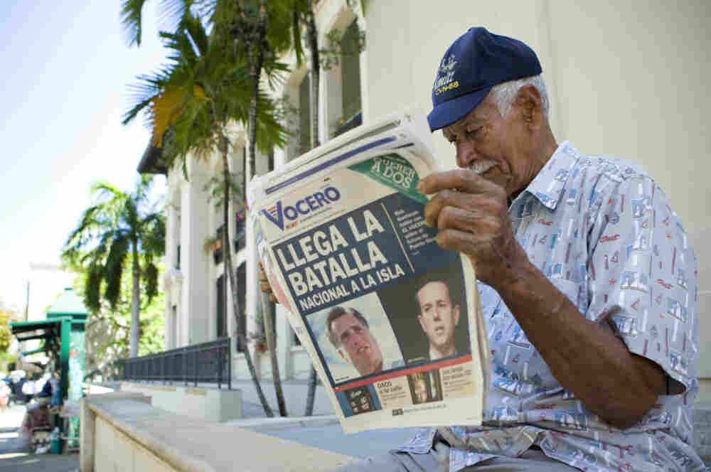 """Carlos Diaz, 84, reads local newspaper """"El Vocero"""" with a front page depicting both Mitt Romney and Rick Santorum and a headline reading, """"The National Battle Arrives on the Island."""""""