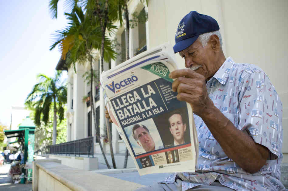 "Carlos Diaz, 84, reads local newspaper ""El Vocero"" with a front page depicting both Mitt Romney and Rick Santorum and a headline reading, ""The National B"