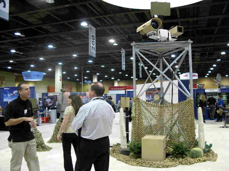 A vendor talks to attendees at the  Border Security Expo in Phoenix, Ariz., next to a display of sophisticated cameras and sensors painted to blend into the desert.