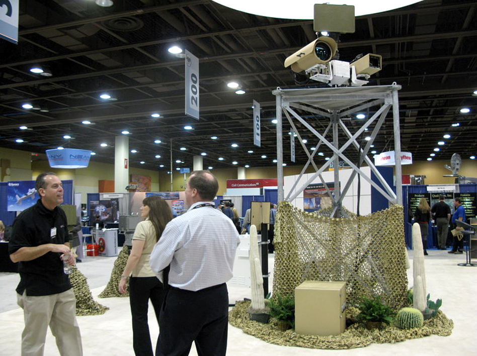 A vendor talks to attendees at the  Border Security Expo in Phoenix, Ariz., next to a display of sophisticated cameras and sensors painted to blend into the desert. (Ted Robbins/NPR)