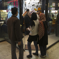 Iranians wait to enter a currency exchange shop in Tehran on Jan. 3. The Iranian rial fell to a record low against the dollar in early January after President Obama signed a bill imposing fresh sanctions on the country's central bank.