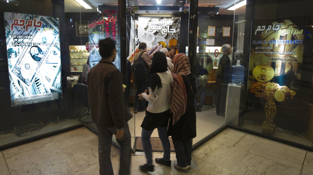Iranians wait to enter a currency exchange shop in Tehran on Jan. 3. The Iranian rial fell to a record low against the dollar in early January after President Obama signed a bill imposing fresh sanctions on the country's central bank.  (Reuters/Landov)