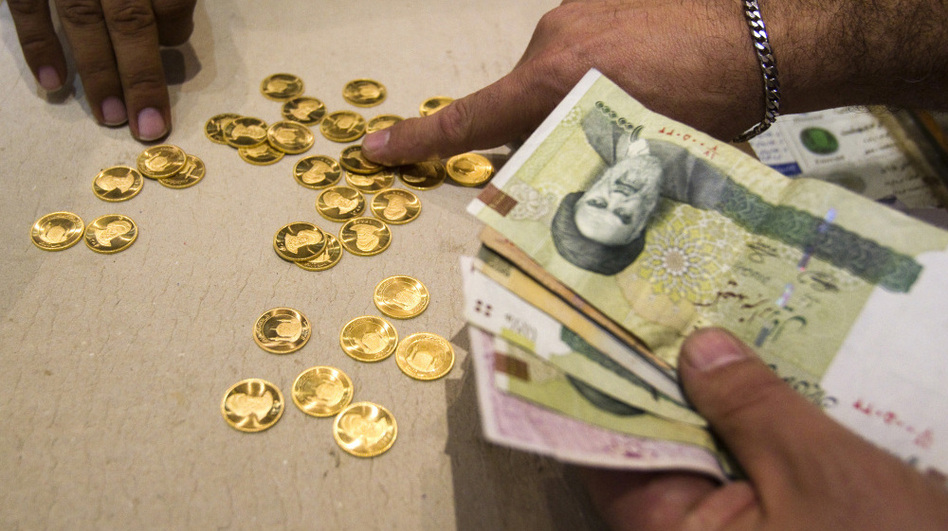 A customer buys Iranian gold coins at a currency exchange office in Tehran. The loss in the rial's value has led Iranians to take their money out of the country — even by speedboat across the Persian Gulf.  (Reuters/Landov)