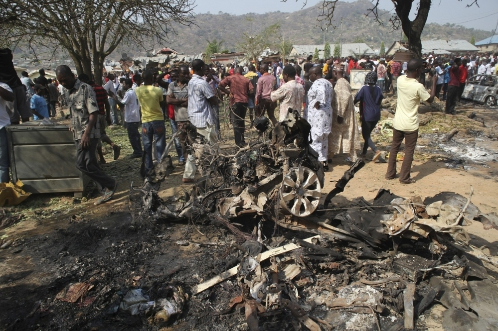 Onlookers view the wreckage of a car bomb that exploded outside a church near Madalla, Nigeria on Christmas Day, 2011 killing scores of people. Boko Haram claimed responsibility for the attack.