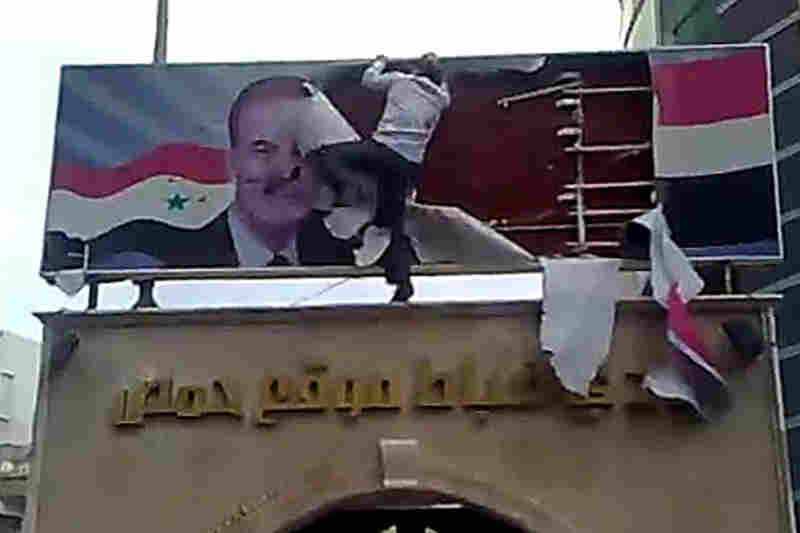 A protester in Homs tears up a poster of ex-president Hafez Assad, who died in 2000, in this AFP image grab from YouTube on March 25.