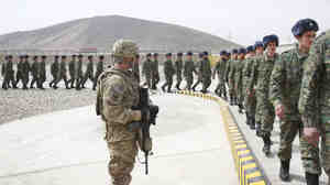 A U.S. soldier watches members of the Afghan Public Protection Force arrive at a ceremony on the outskirts of Kabul on Thursday.