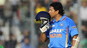 Indian batsman Sachin Tendulkar kisses his helmet after scoring his 100th century (100 runs) today in a match against Bangladesh.