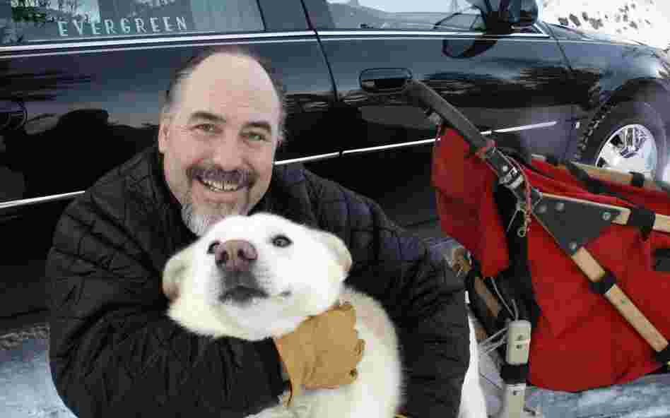 "Iditarod Trail Sled Dog Race rookie Scott Janssen, known as the ""Mushing Mortician,"" of Anchorage, Alaska, poses for a photo with one of his pet dogs."
