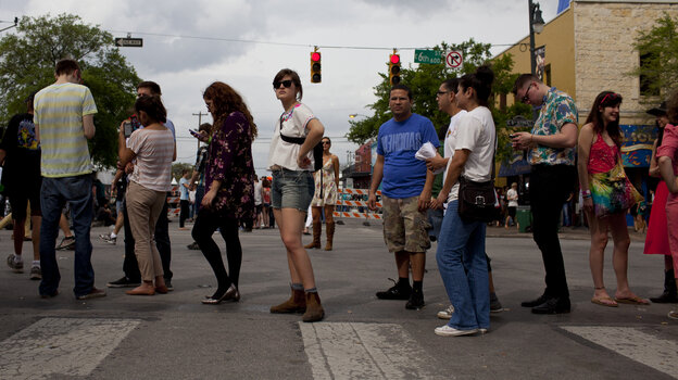 Eventual concertgoers at SXSW wait in line along 6th Street in Austin, Texas.