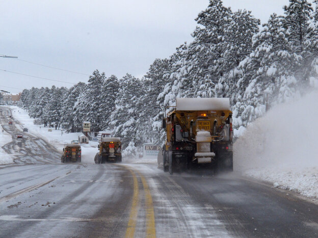 A line of snow plows clears a street on Monday in Flags
