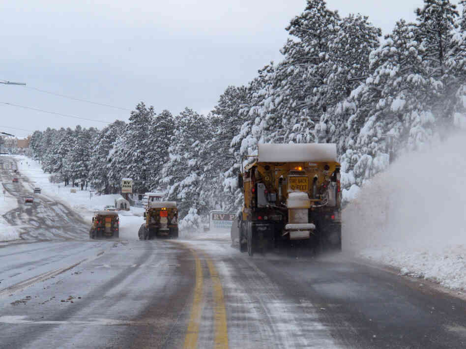 A line of snow plows clears a street on Monday in Flagstaff, Ariz. Heavy snow and high winds struck parts of Arizona