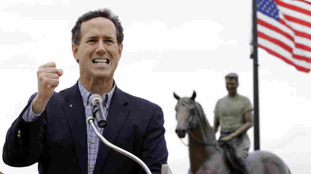 Standing in front of a statue of Ronald Reagan on horseback, Rick Santorum speaks at a campaign rally Monday in Dixon, Ill.