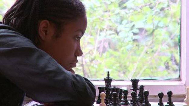 Rochelle, one of the kids in Brooklyn Castle, examines a chess board.