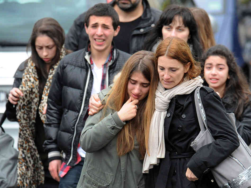 Young people walk away from the Ozar Hatorah Jewish school, on Monday in Toulouse, southwestern France, where at least four people (three of them children) were killed and one seriously wounded when a gunman op