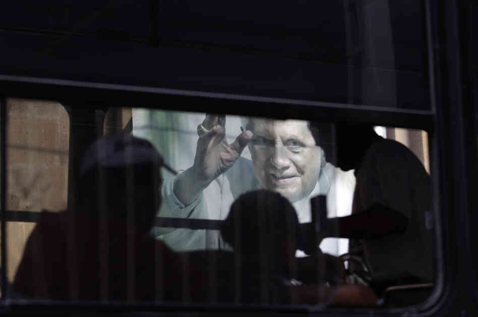 In this Feb. 29, 2012 photo, people riding on a bus pass a banner of Pope Benedict XVI on the wall of a church in Leon, Mexico.
