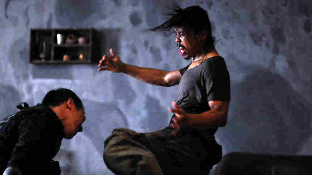 Gang enforcer Mad Dog (Yayan Ruhian, right) fights off Indonesian SWAT agent Jaka (Joe Taslim) as Jaka's team invades a Jakarta tenement controlled by a brutal gangster.