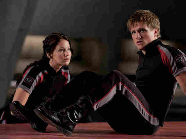 In The Hunger Games, Katniss (Jennifer Lawrence) and Peeta (Josh Hutcherson) train to compete against other teenagers in a fight to the death that all citizens of a ruined North American dystopia must watch.