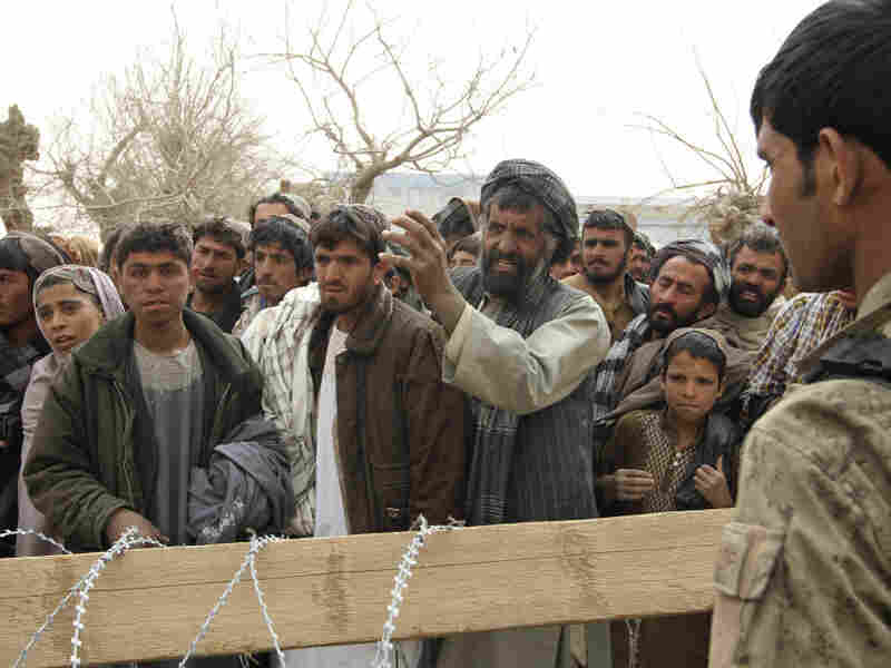 Afghans gather outside a military base in the Panjwai district in Afghanistan on March 11, after 16 civilians were killed in a massacre allegedly carried out by a U.S. soldier.