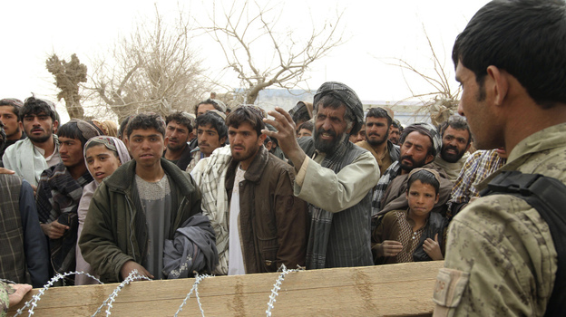Afghans gather outside a military base in the Panjwai district in Afghanistan on March 11, after 16 civilians were killed in a massacre allegedly carried out by a U.S. soldier.   (AP)