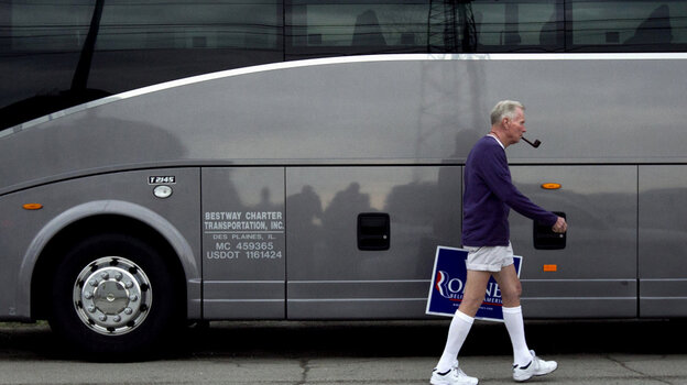 Jim Wilson of Buckingham, Va., who supports Republican presidential candidate Mitt Romney, walks past a bus during a Romney campaign stop Monday in Springfield, Ill.