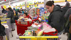 Concepsion Alcantar-Alvarez looks through her cart in the check-out line at a Food 4 Less store in Chicago.