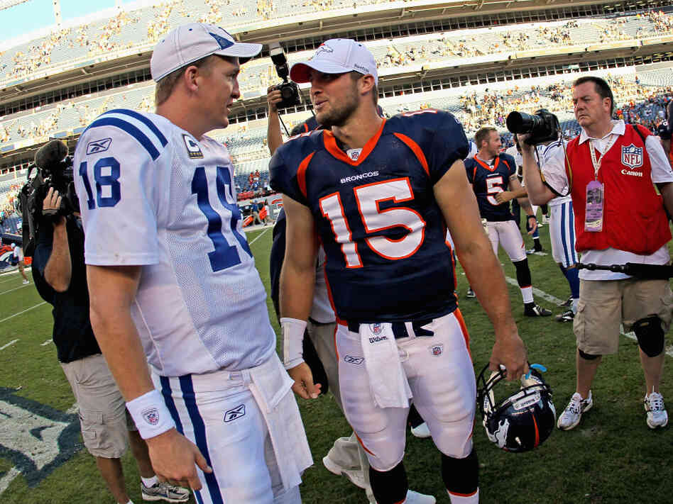 Former Indianapolis quarterback Peyton Manning (left) talks with Tim Tebow of the Denver Broncos in 2010. Manning will be taking Tebow's job.