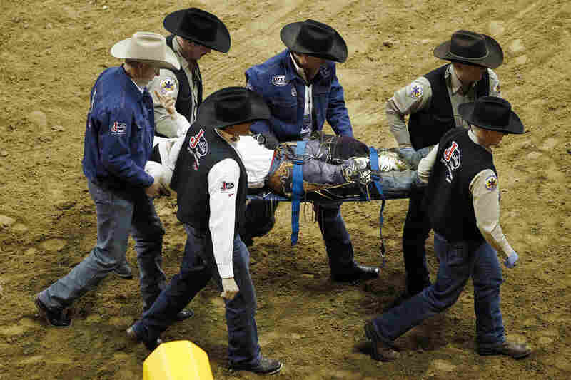 Steve Woolsey signals to the crowd after taking a hoof to the back of the head in the Bull Riding event during the 10th go-round of the National Finals Rodeo in 2010, in Las Vegas. Woolsey received a concussion and contusions.