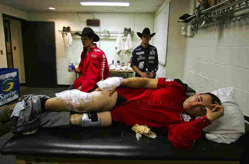 Allan Moraes lies with ice packs on his hand and knee after injuring himself riding a bull.